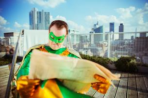 Superhero reading newspaper on city rooftopの写真素材 [FYI02191902]