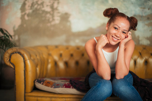 Portrait smiling, confident young woman sitting on sofaの写真素材 [FYI02191904]