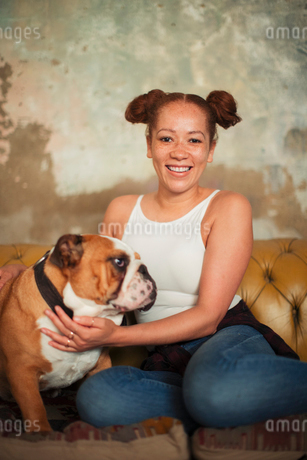 Portrait smiling young woman petting dog on sofaの写真素材 [FYI02191926]