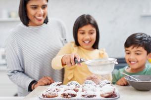 Mother and children baking muffins in kitchenの写真素材 [FYI02191956]