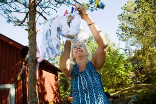 Sweden, Uppland, Runmaro, Woman hanging her laundry outdoorsの写真素材 [FYI02191959]