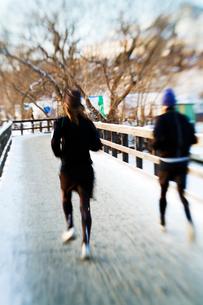 Sweden, Stockholm, Mid adult couple jogging on bridge in winの写真素材 [FYI02191966]