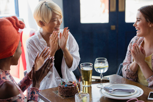 Happy young women friends celebrating birthday in restaurantの写真素材 [FYI02191975]