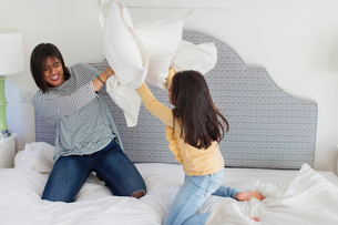 Playful mother and daughter enjoying pillow fightの写真素材 [FYI02191976]