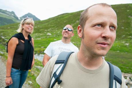 Austria, Osterrike, Vorarlberg, Three people hiking in Alpsの写真素材 [FYI02192037]