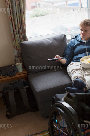Young woman watching TV with feet up on wheelchairの写真素材 [FYI02192055]