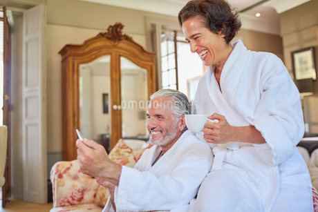 Happy mature couple in spa bathrobes drinking coffee in hotel roomの写真素材 [FYI02192069]