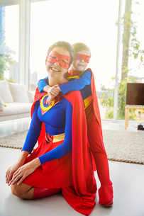 Superhero mother and son smiling in living roomの写真素材 [FYI02192073]