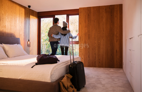 Couple with suitcase looking out bedroom windowの写真素材 [FYI02192124]