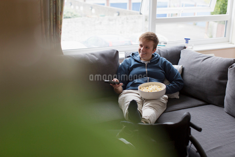 Young woman watching TV and eating popcorn on sofa with feet up on wheelchairの写真素材 [FYI02192161]