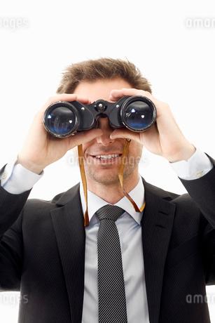 Man looking through binocularsの写真素材 [FYI02192202]
