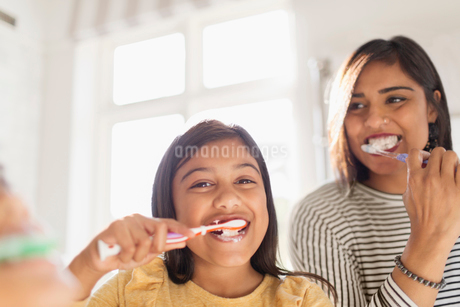 Portrait happy mother and daughter brushing teeth in bathroomの写真素材 [FYI02192222]