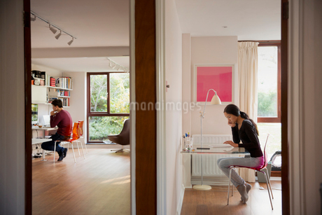 Couple working in bedroom and home officeの写真素材 [FYI02192268]