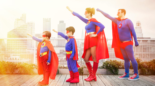 Superhero family standing with arms outstretched on city rooftopの写真素材 [FYI02192293]