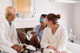 Young women friends wearing eye masks in bedroomの写真素材 [FYI02192355]