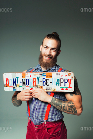 Portrait confident hipster man holding  Dont Worry Be Happy  license platesの写真素材 [FYI02192408]
