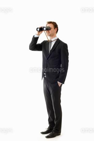 Man looking through binocularsの写真素材 [FYI02192417]