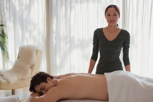 Portrait confident female masseuse giving man massageの写真素材 [FYI02192467]