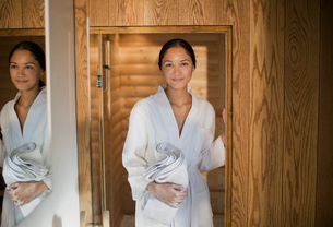 Portrait young woman in bathrobe standing in spa doorwayの写真素材 [FYI02192489]