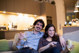 Happy couple drinking white wine and watching TV on apartment sofaの写真素材 [FYI02192521]
