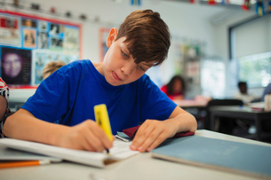 Focused junior high school boy student using highlighter, doing homework in classroomの写真素材 [FYI02192539]