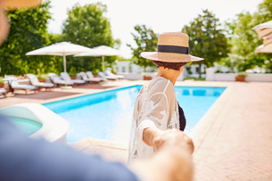 Mature couple holding hands at sunny poolsideの写真素材 [FYI02192573]