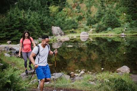 Couple hiking along lake in woodsの写真素材 [FYI02192580]
