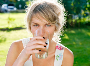 Sweden, Vastergotland, Boras, Young woman enjoying cold drinの写真素材 [FYI02192614]
