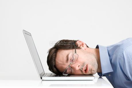 Man sleeping at desk with laptopの写真素材 [FYI02192640]
