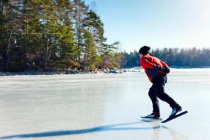 Sweden, Uppland, Loparo, Man ice-skating on frozen lakeの写真素材 [FYI02192733]