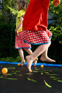 Sweden, Two girls (4-5) jumping on trampolineの写真素材 [FYI02192787]