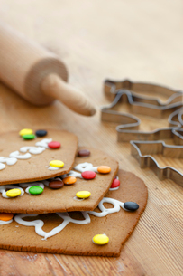 Rolling pin, pastry cutters, and cookies on cutting boardの写真素材 [FYI02192808]