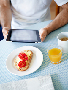 Midsection of man using tablet pc at breakfast tableの写真素材 [FYI02192907]