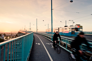 Sweden, Goteborg, Men cycling on bridgeの写真素材 [FYI02192959]