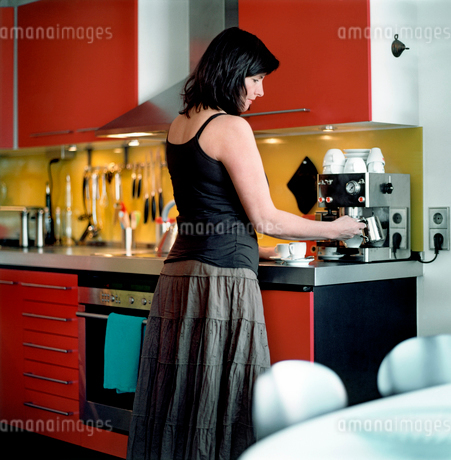 Woman making coffee in kitchenの写真素材 [FYI02193023]