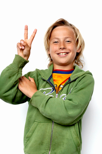 Studio portrait of boy (8-9) showing peace signの写真素材 [FYI02193077]