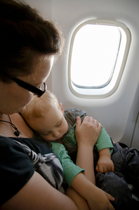 Boy (2-3) travelling by plane with his motherの写真素材 [FYI02193159]