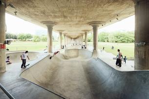 Sweden, Stockholm, Young men skateboarding under bridgeの写真素材 [FYI02193182]