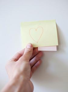 Human hand holding adhesive note, studio shotの写真素材 [FYI02193207]