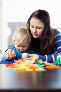 Finland, Mother helping daughter (2-3) with painting Easterの写真素材 [FYI02193394]