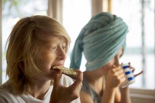 Finland, Teenage boy ( 16-17 ) and girl ( 10-11 ) eating breの写真素材 [FYI02193403]