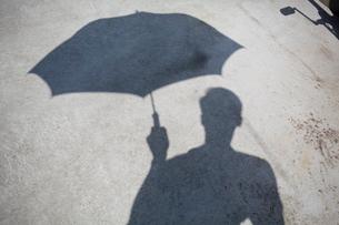 Shadow of man holding umbrellaの写真素材 [FYI02193489]