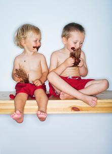 Finland, Portrait of boys (2-3), (4-5) eating chocolateの写真素材 [FYI02193506]