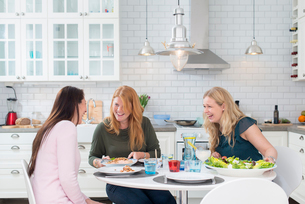 Sweden, Three laughing women at kitchen tableの写真素材 [FYI02193575]