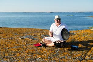 Sweden, Sodermanland, Stockholm Archipelago, Varmdo, Mature man grilling sausage on rocky beachの写真素材 [FYI02193614]