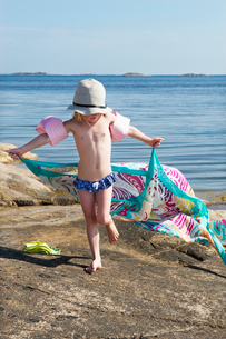 Sweden, Sodermanland, Stockholm Archipelago, Varmdo, Girl (4-5) playing with shawl on rocky beachの写真素材 [FYI02193770]