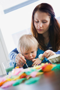 Finland, Mother helping daughter (2-3) with painting Easterの写真素材 [FYI02193780]