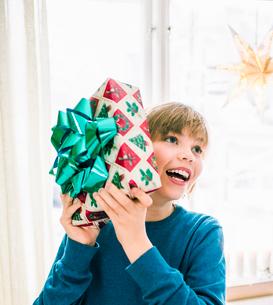 Boy (10-11) shaking Christmas presentの写真素材 [FYI02193793]