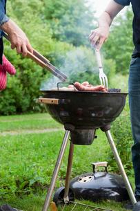 Sweden, Ostergotland, Vikbolandet, Mid-adult men having barbecue in backyardの写真素材 [FYI02193974]