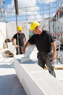 Sweden, Ostergotland, Linkoping, Construction workers preparing building blocks to build wallの写真素材 [FYI02193999]